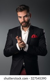 Man's style. Elegant young man in a suit posing. Studio shot.