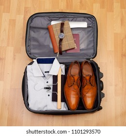 Man's suitcase for short vacation or city trip on wooden floor