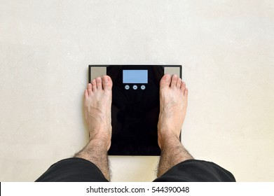 Man's view of his feet standing on a black bathroom scale