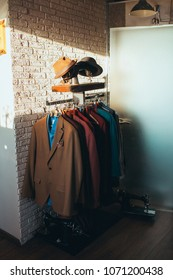 man's wardrobe with different color suits and hats. Located in the loft style room near brick wall