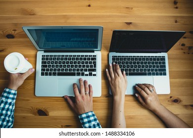 Man's and woman's hands using laptop with blank screen on desk in home interior with cup of coffee.