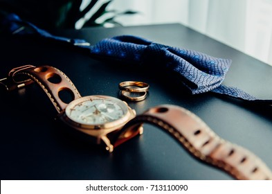 A man's and woman's wedding rings . A man's wrist watch is in the background out of focus.