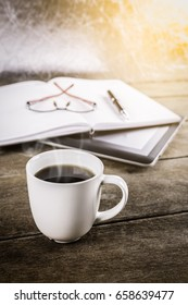 mans working place at wooden desktop with coffee. Office desk table with tablet,, glasses, notebook, cup of coffee. Top view with copy space