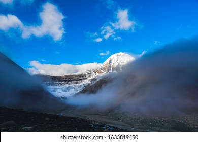 Mansarovar, China - 15 Aug 2018 - The Peak of Kailash Mansarover over the clouds on a blue day covered in snow & ice