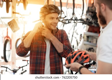 The man-seller shows the buyer a helmet for bike rides. A young man came to the bicycle store. He is measuring the helmet.