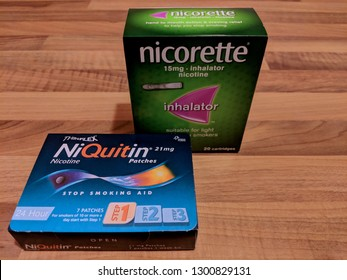 MANSFIELD, ENGLAND - JANUARY 01, 2018:  Smoking cessation aids - NiQuitin nicotine replacement patches and Nicorette inhalator - on a wood laminate work surface
