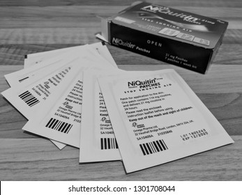 MANSFIELD, ENGLAND - JANUARY 01, 2018:  Smoking cessation aids - NiQuitin nicotine replacement patches fanned out on a wood laminate work surface in front of their box
