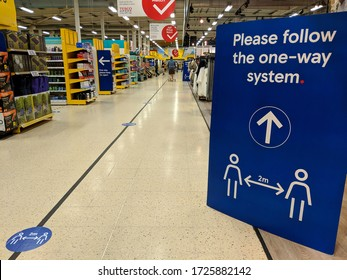 "MANSFIELD, UK - APRIL 14, 2020:  One-way system sign and ""social distancing, 2 metres apart"" floor markings in the aisle of a branch of Tesco supermarket chain during COVID-19 Pandemic"