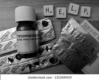 """MANSFIELD, UK - FEBRUARY 14, 2019: """"HELP"""" alongside a cocktail of prescription medication. Diazepam, Seroxat (Paroxetine) and Lofepramine in foil packs & bottle with child proof cap (Black and White)"""