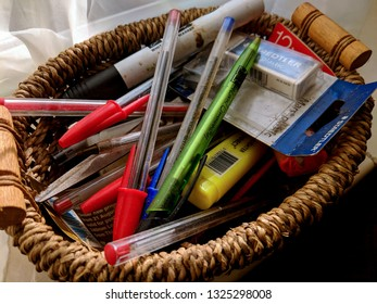 MANSFIELD, UK - FEBRUARY 28, 2019:  Small wicker basket full of pens, biros, felt tips, marker pens, pencils, erasers and sharpeners