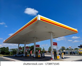 MANSFIELD, UK - MAY 9, 2020: Shell petrol station forecourt, 4 V-Power pumps, a car refueling under a large steel fabricated canopy. Cars and a van being clean in background, during COVID-19 Pandemic