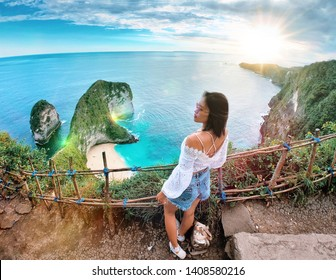 Manta Bay or Kelingking Beach on Nusa Penida Island, Bali, Indonesia. Asian girl in  an amazing wild nature view sandy beach with rocky mountains and azure lagoon with clear water of Indian ocean at s