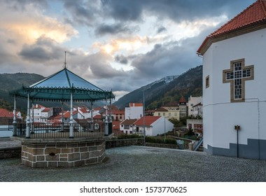 Manteigas village bandstand with houses and mountains in the background under dramatic sky, cross of Stª Maria Mother Church visible in the photo, PORTUGAL