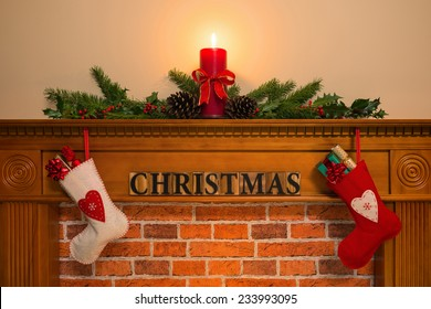 Mantelpiece with red candle and fresh garland made from holly, two stockings full of gifts hanging over the fireplace with the word Christmas.