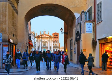 Mantova, Italy 24.02.2019. People on street, old arch with Duomo in background in Mantua, Lombardy, Italy