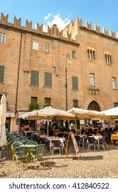 MANTOVA, ITALY - APRIL 20, 2016: People sitting by a restaurant in front of a building on a square