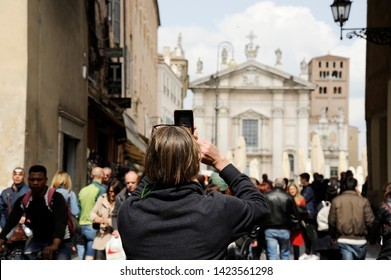 Mantova, Italy - April 22, 2019: Close-up of man tourist on the street in Mantua, taking photo of Piazza Sordello with the phone. Mantua, Italy