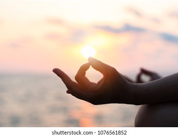 Mantra yoga meditation, spiritual mental health practice with silhouette of woman in lotus pose having peaceful mind relaxation on the beach outdoor training with sunset golden hour heavenly sky