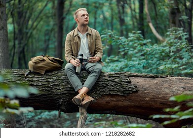 A man-traveler sits on a large fallen tree, holding a thermos with hot tea in his hand. He wears brown boots, a shirt, a t-shirt and a backpack next to him.