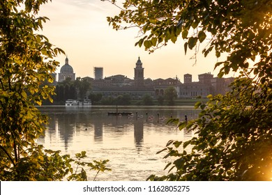 Mantua city skyline reflected in lake, framed by tree branches, evening
