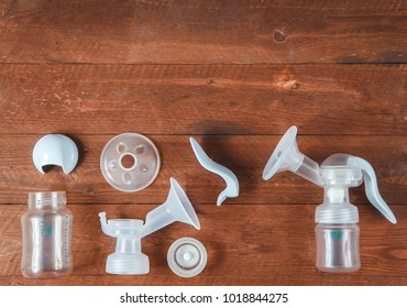 manual breast pump and parts on wooden table. Copy space.