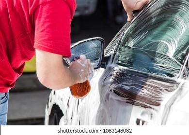 Manual car wash. Man washing his car with foam.