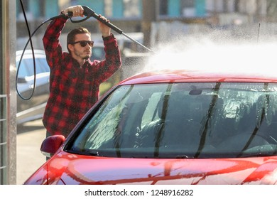 Manual car wash with pressurized water in car wash outside.Summe Washing. Cleaning Car Using High Pressure Water. Washing car with soap. Close up concept.
