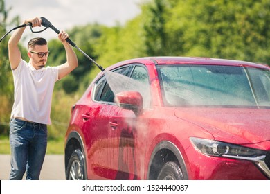 Manual car wash with pressurized water in car wash outside. Summer Car Washing. Cleaning Car Using High Pressure Water. Washing  with soap. Close up concept.