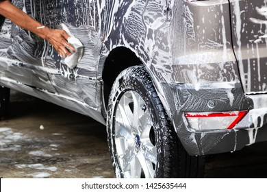 Manual car wash in car wash shop service with employee worker in back.
