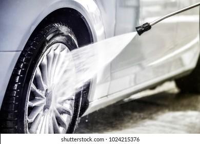 Manual car washing with water jet. Car wash wheel detail. Clean car at wash station.
