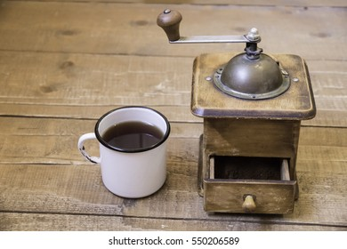 Manual coffee grinder and a cup of coffee on a wooden surface