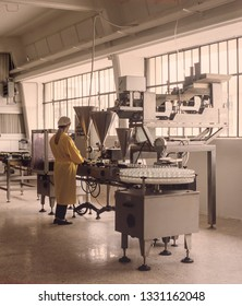 manual female worker on semi automatic filling machine, interior of a production factory