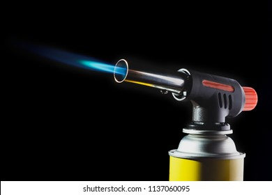 manual gas burner with blue flame on the black bacground