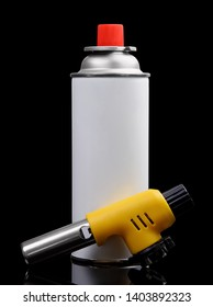 Manual gas torch burner (blowtorch) for camping, soldering or repair and gas spray can isolated on black background.