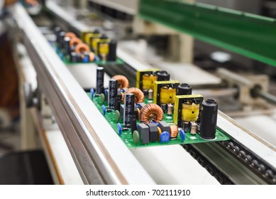 Manual insertion of electronic components on printing circuit board assembly before wave soldering. The image taken in a electronic production plat on a conveyor belt.