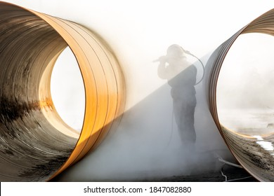 Manual sandblasting or abrasive blasting to metal pipe. Abrasive blasting, more commonly known as sandblasting, is the operation of forcibly propelling a stream of abrasive material against a surface.