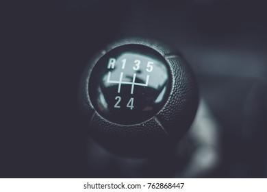 Manual shifting gear stick on black dark background.