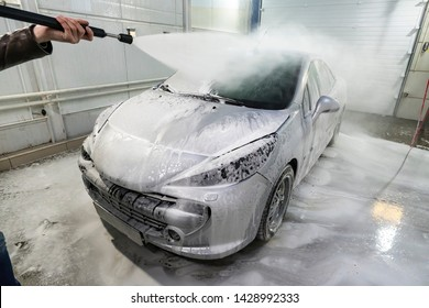 Manual sport car wash. Washing luxury vehicle with high pressure water pump. Automobile cleaning self service. water wash foam off the car. man worker washes the car.