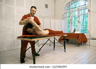 Manual therapist and caucasian male patient at bending back procedure. Horizontal shot