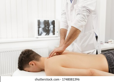 Manual therapist doing manual adjustment on patient's spine. Chiropractic, osteopathy, manual therapy, post traumatic rehabilitation, sport physical therapy. Alternative medicine, pain relief concept.