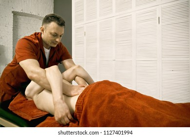 Manual therapist pressing on caucasian male patient back standing at his head. Closeup horizontal shot