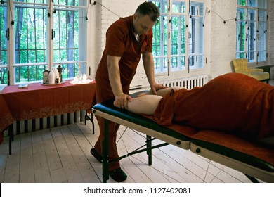 Manual therapist pressing on woman legs. Horizontal shot