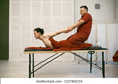 Manual therapist pulling back caucasian male patient. Horizontal sideview shot