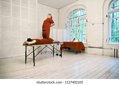 Manual therapist standing on caucasian male patient back. Horizontal shot