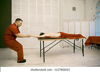 Manual therapist stretching caucasian male patient pulling his arm. Sideview horizontal shot