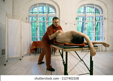 Manual therapist stretching caucasian male patient body. Horizontal shot