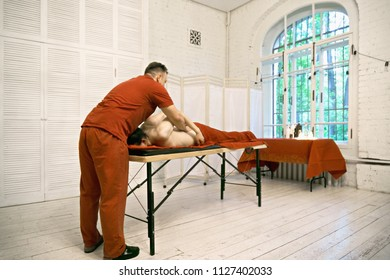 Manual therapist treating caucasian male patient shoulders standing at his head. Horizontal shot