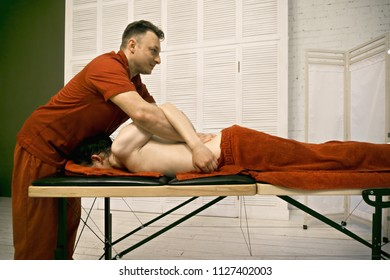 Manual therapist working with caucasian male patient back standing at his head. Sideview horizontal shot
