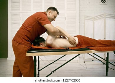 Manual therapist working with caucasian male patient shoulders standing at his head. Sideview horizontal shot