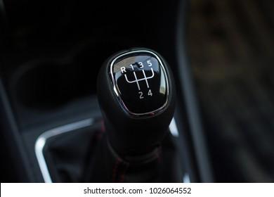 manual transmission gear shift, on dark backgroun.